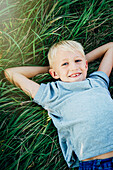 Caucasian boy laying in tall grass