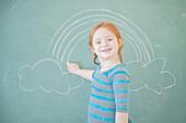Caucasian girl drawing on chalkboard
