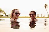Smiling women swimming in infinity pool