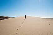Caucasian teenage boy running on sand dune