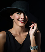 Stylish Caucasian woman wearing black hat and dress