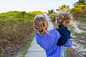 Caucasian girl carrying baby brother on wooden walkway