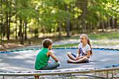 Caucasian children sitting on trampoline