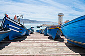 Blue boats docked on boat ramp