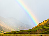 Rainbow over rural fields and hillside, Landmannalaugar, Fjallabak Nature Reserve, Iceland