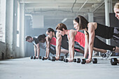 Athletes doing push-ups with dumbbells on floor