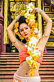 Asian woman standing on stairs of ornate Buddhist temple, Chiang Mai, Chiang Mai, Thailand