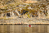 People paddling canoe near rock formations in remote river