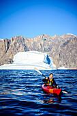 Woman paddling canoe near glaciers in remote river