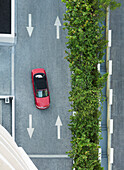 Aerial view of car driving on street with arrows