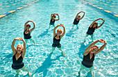 Older Caucasian women taking fitness class in swimming pool
