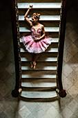 Hispanic ballet dancer posing on staircase