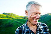 Older Caucasian man smiling on rural hilltop