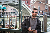 Caucasian man holding cell phone on dock, Venice, Veneto, Italy