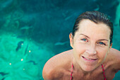 Caucasian woman smiling in swimming pool