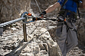 Caucasian climber hooked to stakes on mountain slope