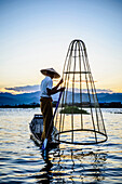 Asian fisherman using fishing net in canoe on river