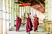 Asian monks-in-training playing with parasols in hallway