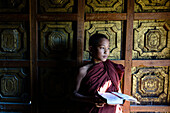 Asian monk-in-training holding book in temple