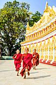 Asian monks-in-training running outside ornate temple