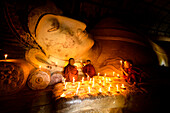 Asian monks-in-training lighting candles at Buddha statue