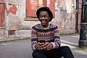 Black man using cell phone on urban sidewalk