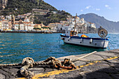 Tethered fishing boat with rope, Amalfi harbour, from quayside with view towards Amalfi town, Costiera Amalfitana (Amalfi Coast), UNESCO World Heritage Site, Campania, Italy, Europe