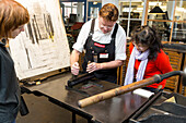 Visitor and worker printing using a print roller, Museum of Printing Arts Leipzig, Leipzig, Saxony, Germany