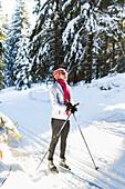 Women skiing, taking a rest, winter forest, cross-country ski run, MR, Holzhau, Saxony, Germany