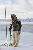 Inuit or Inughuit subsistence hunter in traditional clothing for winter and spring of seal skin boots (Kamiks), polar bear fur trousers, seal skin mitts and parka, Greenland, Denmark, Polar Regions