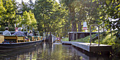 Lock with boat landing, people in canoes and kayaks on a stream in Unterspreewald, biosphere reserve,  Schlepzig, Brandenburg, Germany