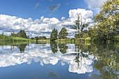 Blick auf auf die Flusslandschaft des Unterspreewaldes bei Windstille und Sonnenschein. Wolken, Bäume und Himmel spiegeln sich in der Wasseroberfläche, Biosphärenreservat, Schlepzig, Brandenburg, Deutschland