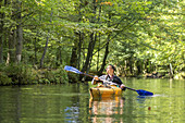 Kayak tourist paddling on a branch stream. The sun shines through the forest, biosphere reserve, Schlepzig, Brandenburg, Germany