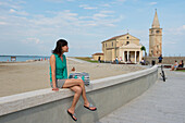Woman sitting on a wall at Madonna dell' Angelo church, Caorle, Venice, Veneto, Italy