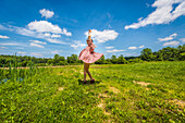 Young Adult Woman in Pink Dress Dancing in Field