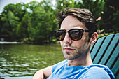 Young Adult Man in Sunglasses Looking Serious by Lake