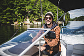 Smiling Young Adult Man in Wool hat Driving Motor Boat on Lake