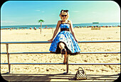 Portrait of Young Adult Woman in Sunglasses and Retro Dress on Boardwalk at Beach