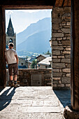 Mid-Adult Man Looking at Panoramic View from Village Doorway, Rear View, Lanslevillard, Val Cenis Vanoise, France