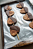 Heart-Shaped Cookies Dipped in Chocolate on Baking Sheet