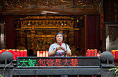 Taiwanese woman is praying in a temple in Taipeh, Taiwan, Republic of China, Asia
