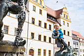 Boy sitting on the fountain outside the town hall, Torgau, Saxony, Germany, Europe
