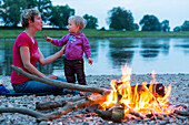 Mother and daughter making bread on a stick on the campfire, Camping along the river Elbe, Family bicycle tour along the river Elbe, adventure, from Torgau to Riesa, Saxony, Germany, Europe