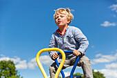 Boy jumping on a seesaw, MR, Riesa, Saxony, Germany, Europe