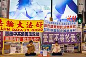 Followers of Falun Gong demonstrating on the street, signs, advertisment of underwear, H&M, meditation, Li Hongzhi, shopping street, street scene, shopping area Causeway Bay, Hong Kong, China, Asia