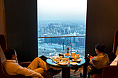 Guest enjoying the view over Beijing, dusk, dinner, man and women, China World Trade Center Tower, restaurant on the top floor, Beijing tallest skyscraper, Beijing, China, Asia