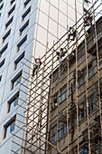 Arbeiter klettern im Bambusgerüst, Abbau, Akrobaten, ohne Sicherung, Fassade, alt, neu, Kontrast, Arbeitssicherheit, Gerüst, Monteure, Rückbau des Baugerüsts, Fassade, Baustelle, Wohnhaus, Hong Kong, Wanchai, Hongkong, China, Asien