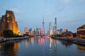 historic Waibaidu steel bridge crosses Suzhou Creek, Broadway Mansions, futuristic Pudong skyline in background, Oriental Pearl Tower, Shanghai Tower, Jin Mao Tower, reflections, Oriental Pearl Tower, evening, city lights, Shanghai, China, Asia