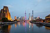 historic Waibaidu steel bridge crosses Suzhou Creek, Broadway Mansions, futuristic Pudong skyline in background, Oriental Pearl Tower, Shanghai Tower, Jin Mao Tower, reflections, Oriental Pearl Tower, evening, city lights, Shanghai, China, Asia
