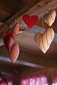 Red heart decorations in felt, fabric and metal hanging from a wooden ceiling beam, Filzmoos, Austria